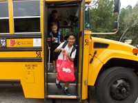 Heavily laden student disembarks