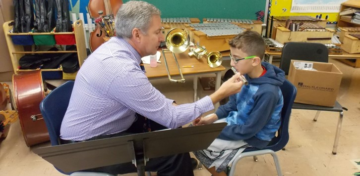 man holds flute mouthpiece for boy to try