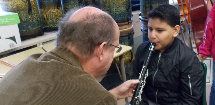 man holds clarinet for student to try