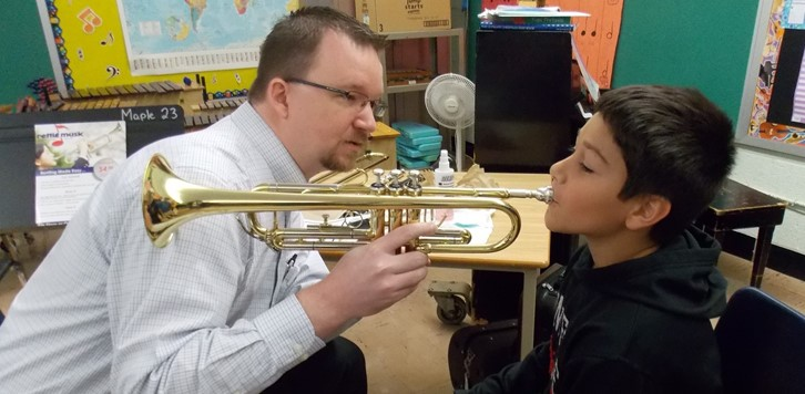 Man holds trumpet for boy to try