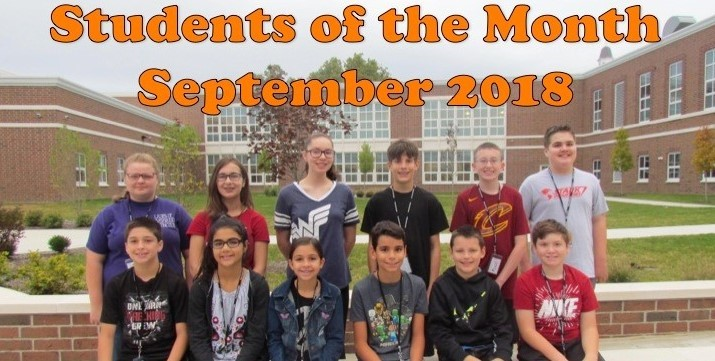 12 students pictured in the courtyard of the middle school