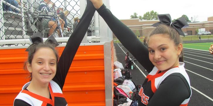 2 cheerleaders holding hands