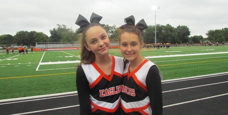 two cheerleaders smile