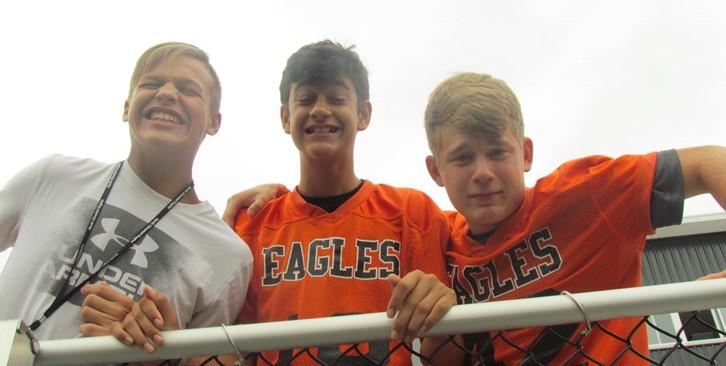 3 boys look down at camera