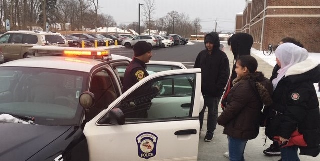 ELL students gather around Officer Carbone's squad car