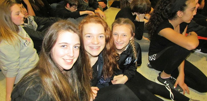 Three students smile for the camera at the school pep rally