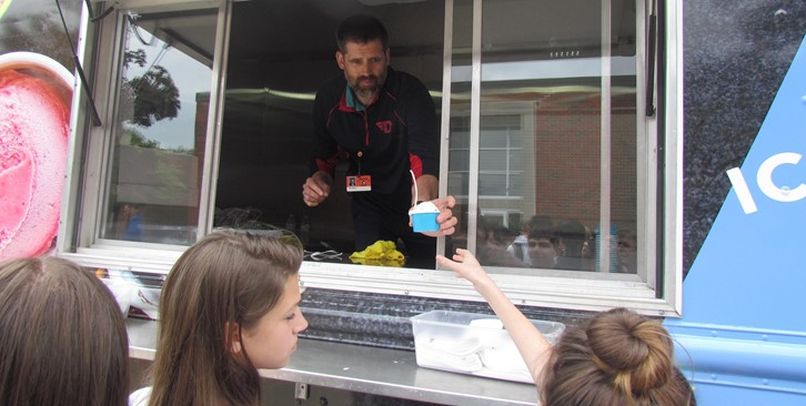 Mr. Busold scoops ice cream for students