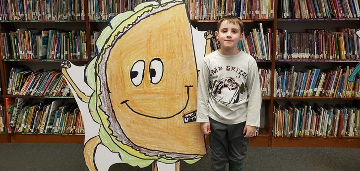 Student with cut-out of super hero