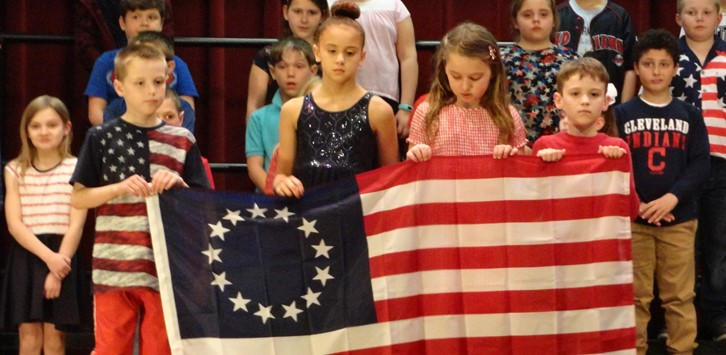 Students holding American flag